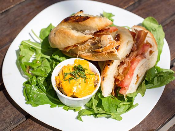 Sándwich de pollo bacon + papas al horno en cubitos con salsa cheddar y verdeo
