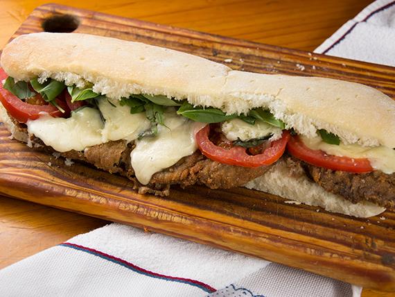Sándwich de milanesa con queso, tomate y albahaca