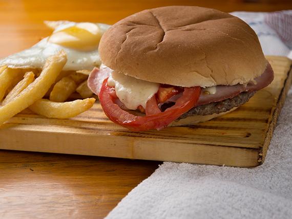 Sándwich de hamburguesa gigante con jamón, queso, tomate, papas fritas y huevo
