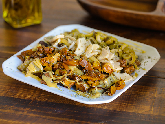 Porción de papas y boniatos horneados con condimentos frescos + queso derretido + gusto