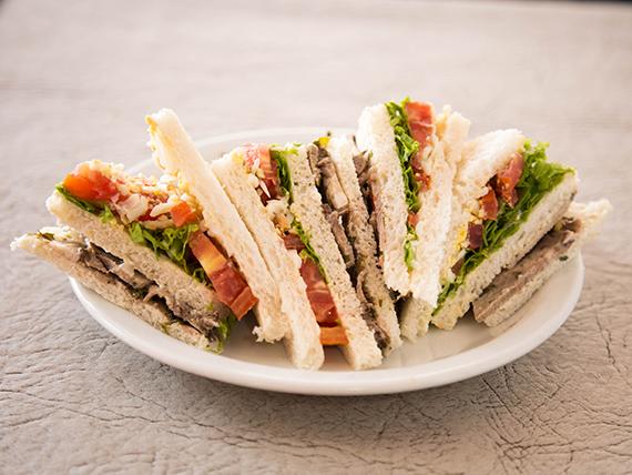 Sándwiche triple de anchoas, lechuga, tomate y manteca