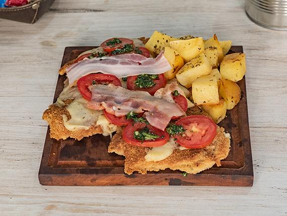 Suprema con panceta, muzzarella, rodajas de tomate y aceitunas acompañada de papitas al horno
