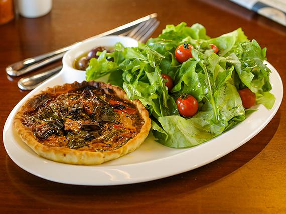 Tarta de vegetales salteados en aceite de ajo y sésamo tostado con hojas verdes y cherry confitado