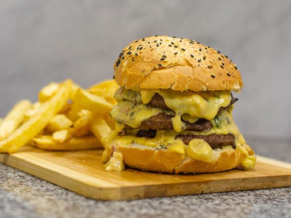 Hamburguesa triple con cheddar, panceta y verdeo con papas fritas