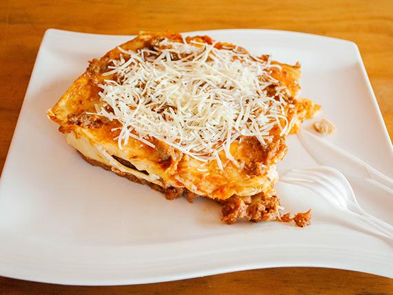 Lasagna con carne, pollo, jamón, queso, salsa bologñesa , salsa alfredo y parmesano