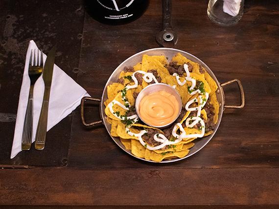 Nachos con cheddar, carne picada, sour cream y jalapeños