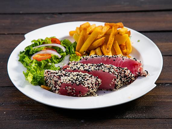 Atún rojo a la plancha con papas fritas y ensalada de lechuga, cebolla morada, tomates cherry y vinagreta