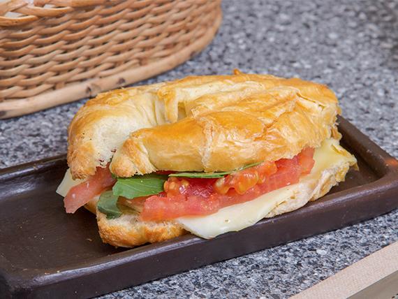 Sándwich croissant de tomate, queso y albahaca