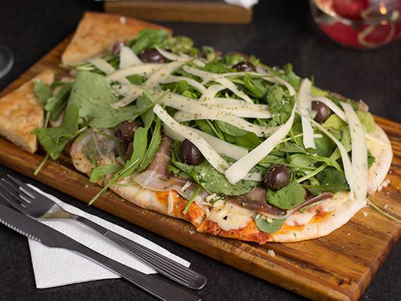Pizza con mozzarella, jamón crudo y rúcula