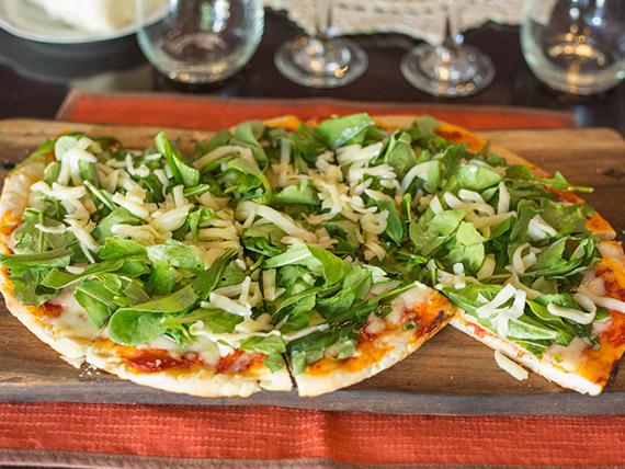 Pizza con rúcula, queso en hebras y olivas